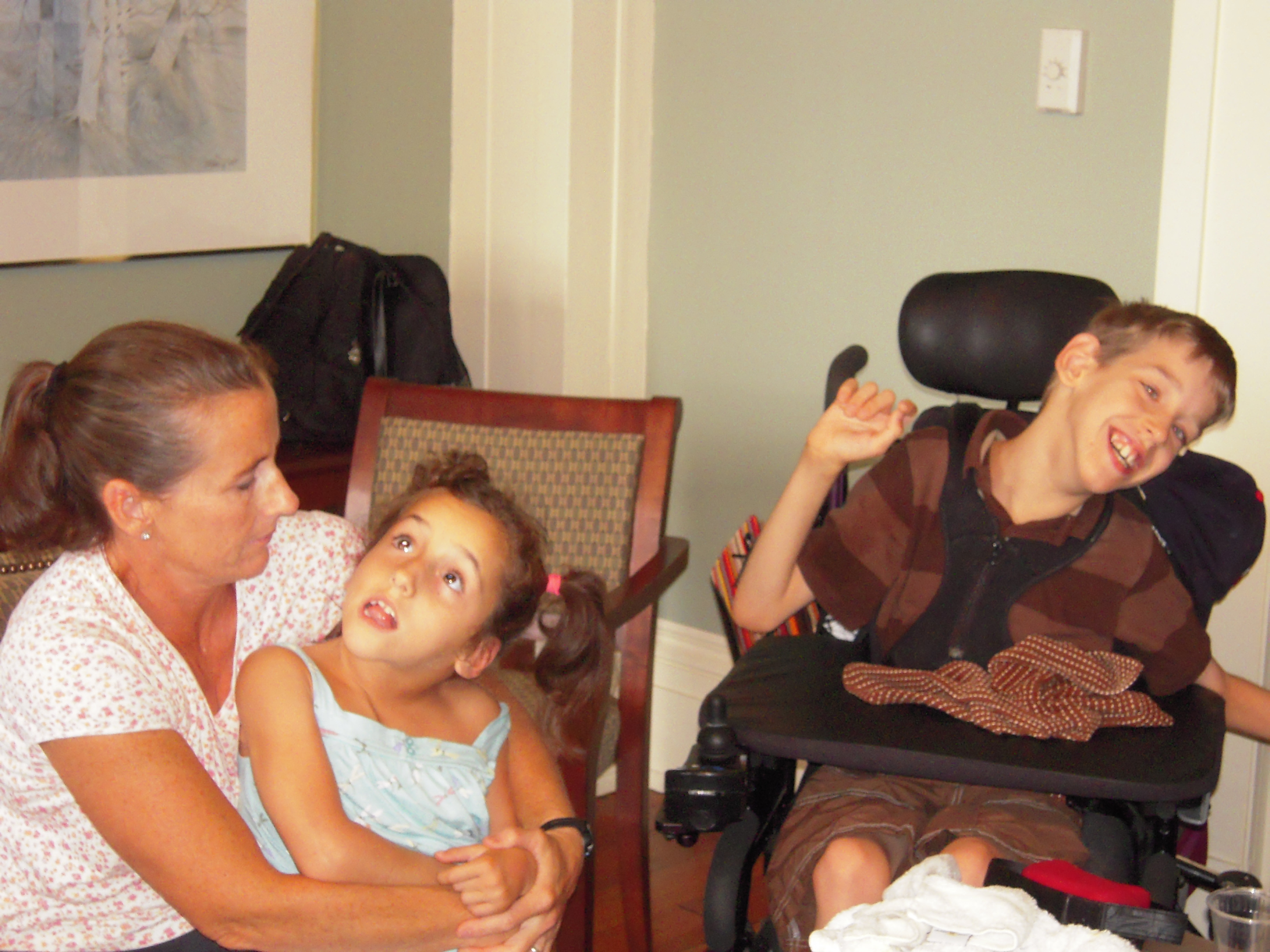 Lexi held by her mom, Justin smiling in his wheelchair