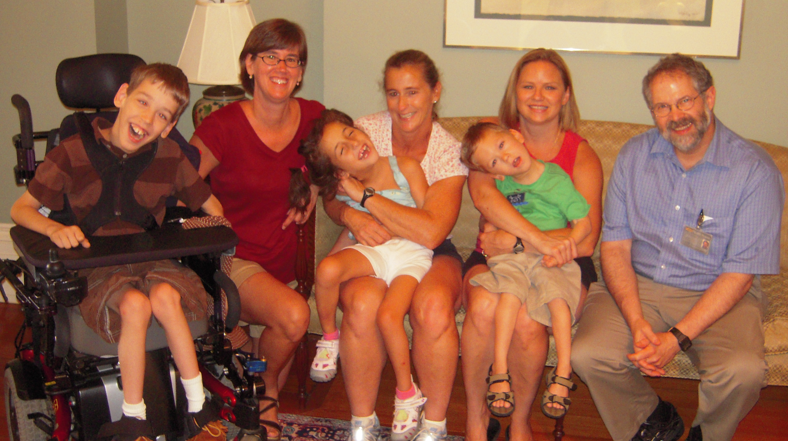 12-year old Justin in wheelchair with mom, Lexi held by her mom, boy held by mom, Dr. Shapiro