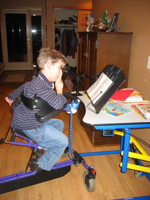 Justin, around 8 years old in gait trainer looking at book on book holder