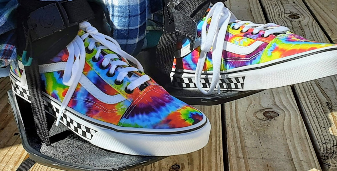 Tie-dye Vans shoes strapped on wheelchair footplates