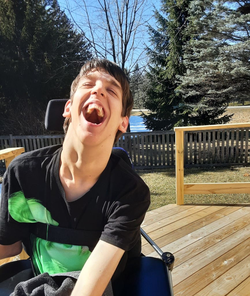 Justin laughing, outside on deck, trees behind