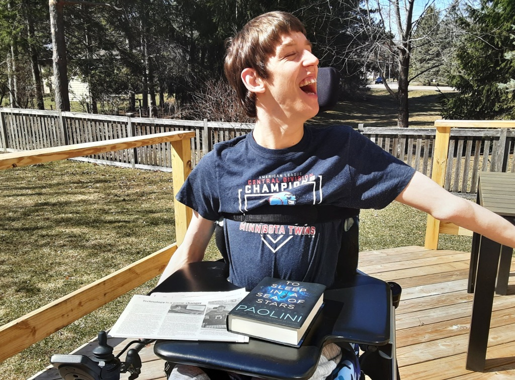 Justin, smiling, seated in power wheelchair on outside deck, To Sleep in a Sea of Stars book by Paolini and newspaper are on lap tray