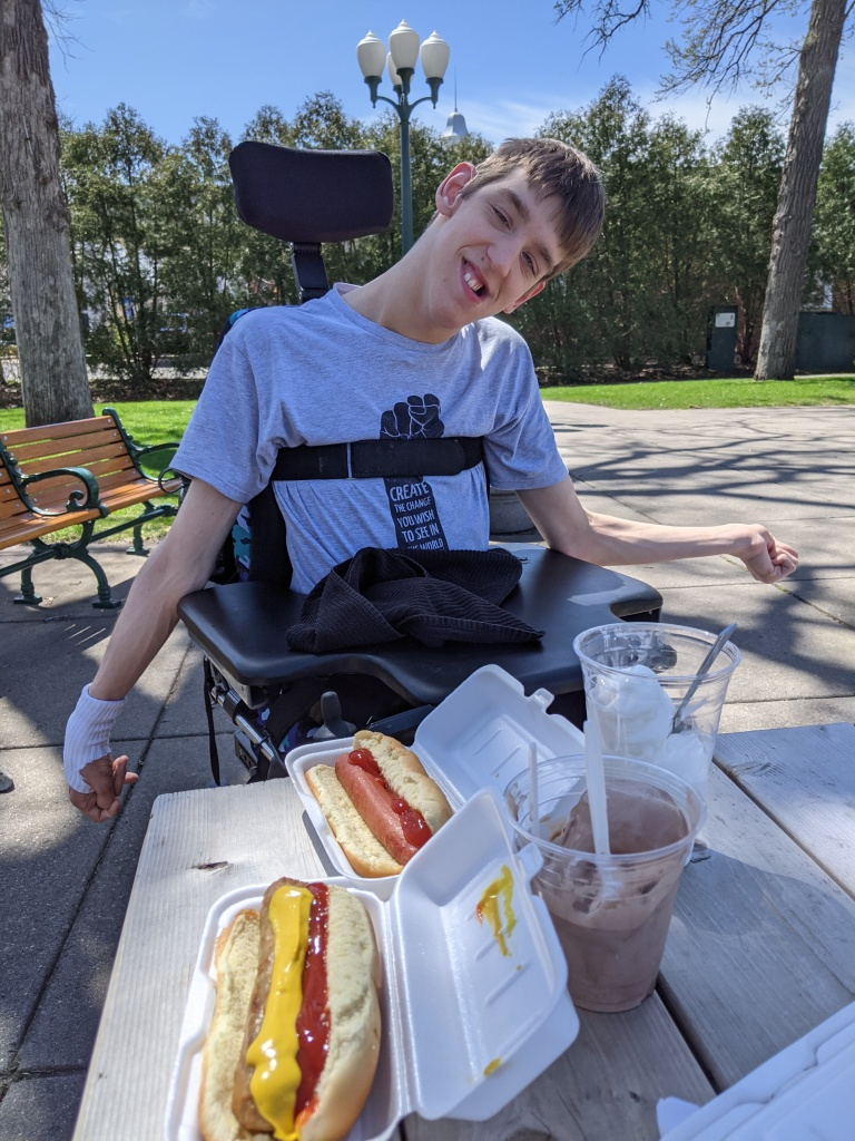 Justin in wheelchair smiling, 2 hot dogs, chocolate and vanilla ice cream in cups on picnic table, trees, park bench