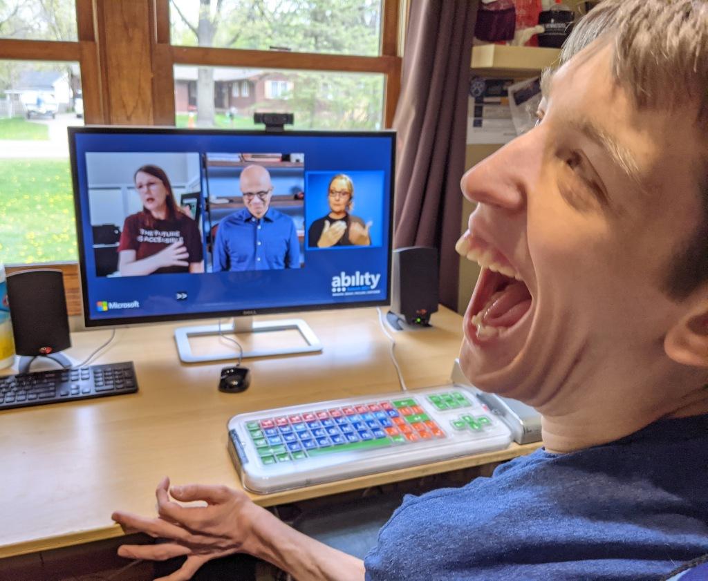 Justin smiling, watching Jenny Lay-Flurry and Satya Nadella and ASL interpreter on computer monitor