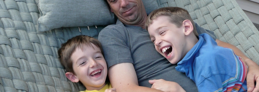 Dad smiling, holding 9-year old laughing Justin and his laughing younger brother on a hammock