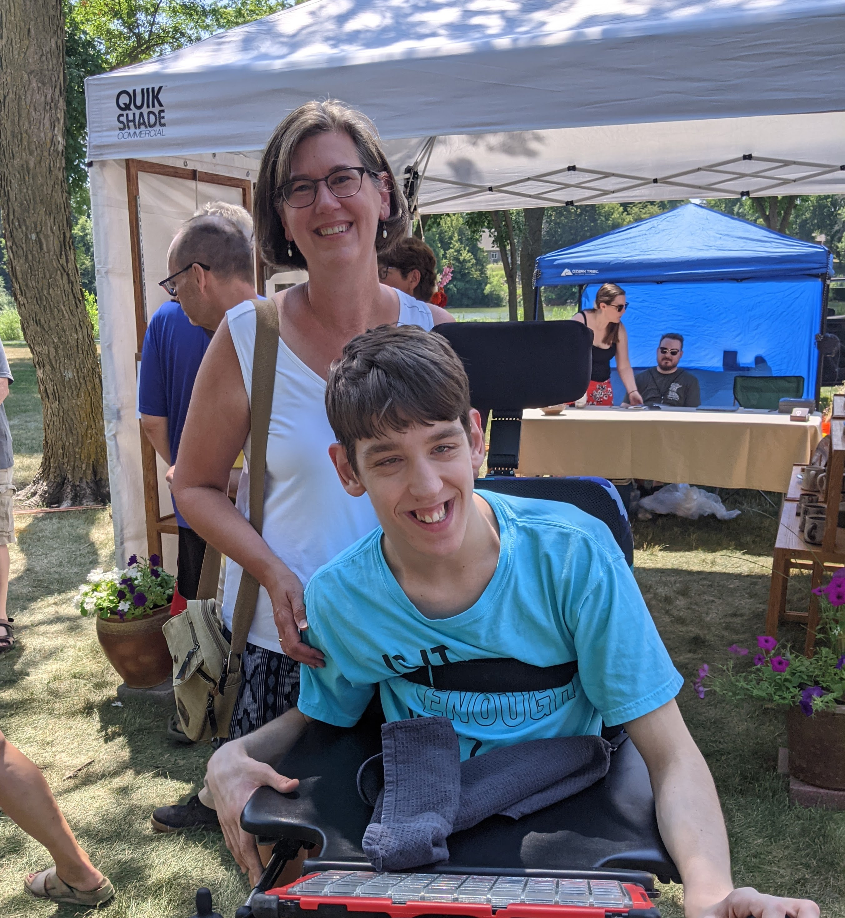 Justin in wheelchair, his mom standing behind, both smiling, people in background looking at pottery booth