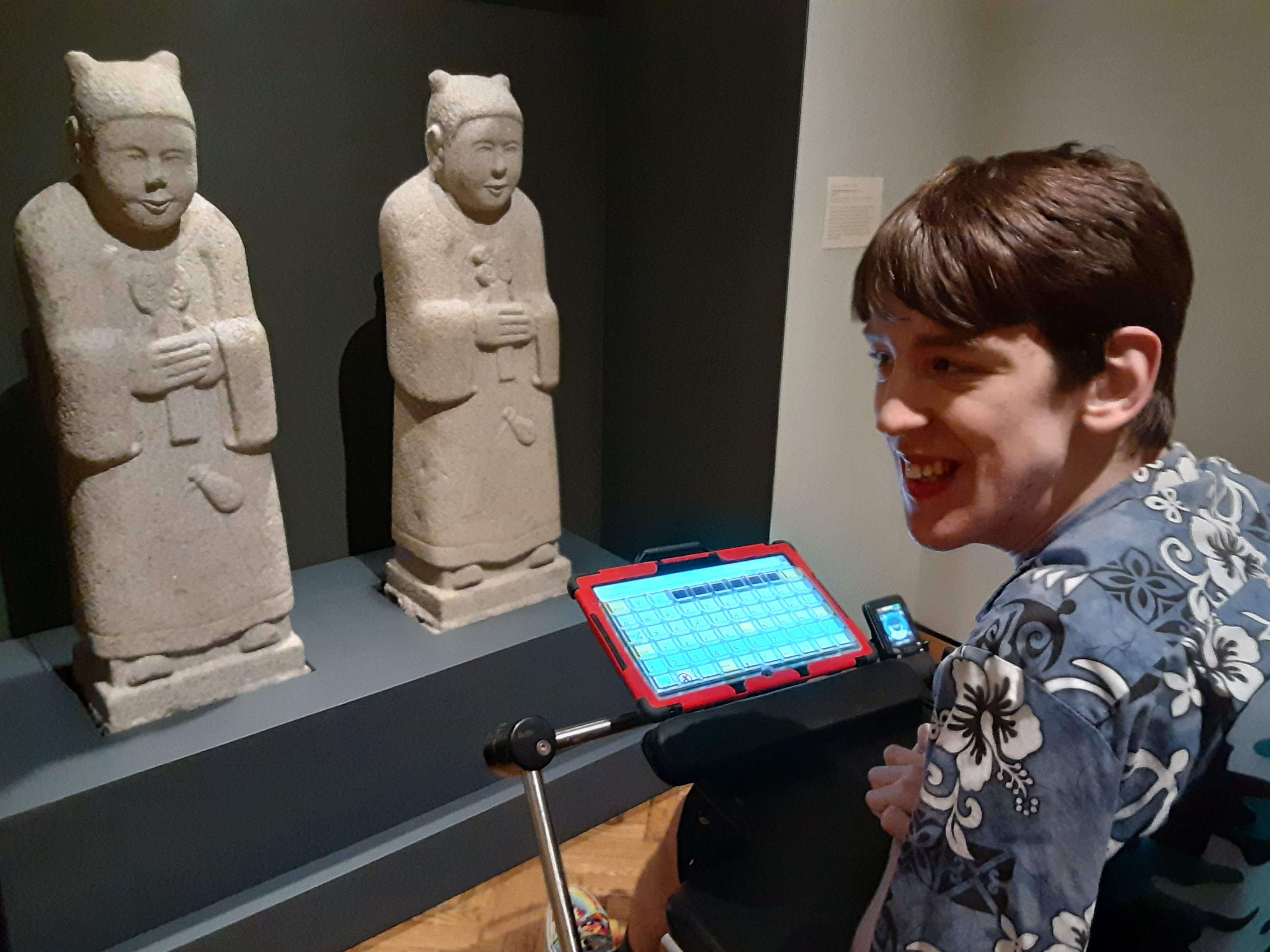 Justin in wheelchair looking at Korean Tomb guardian figures