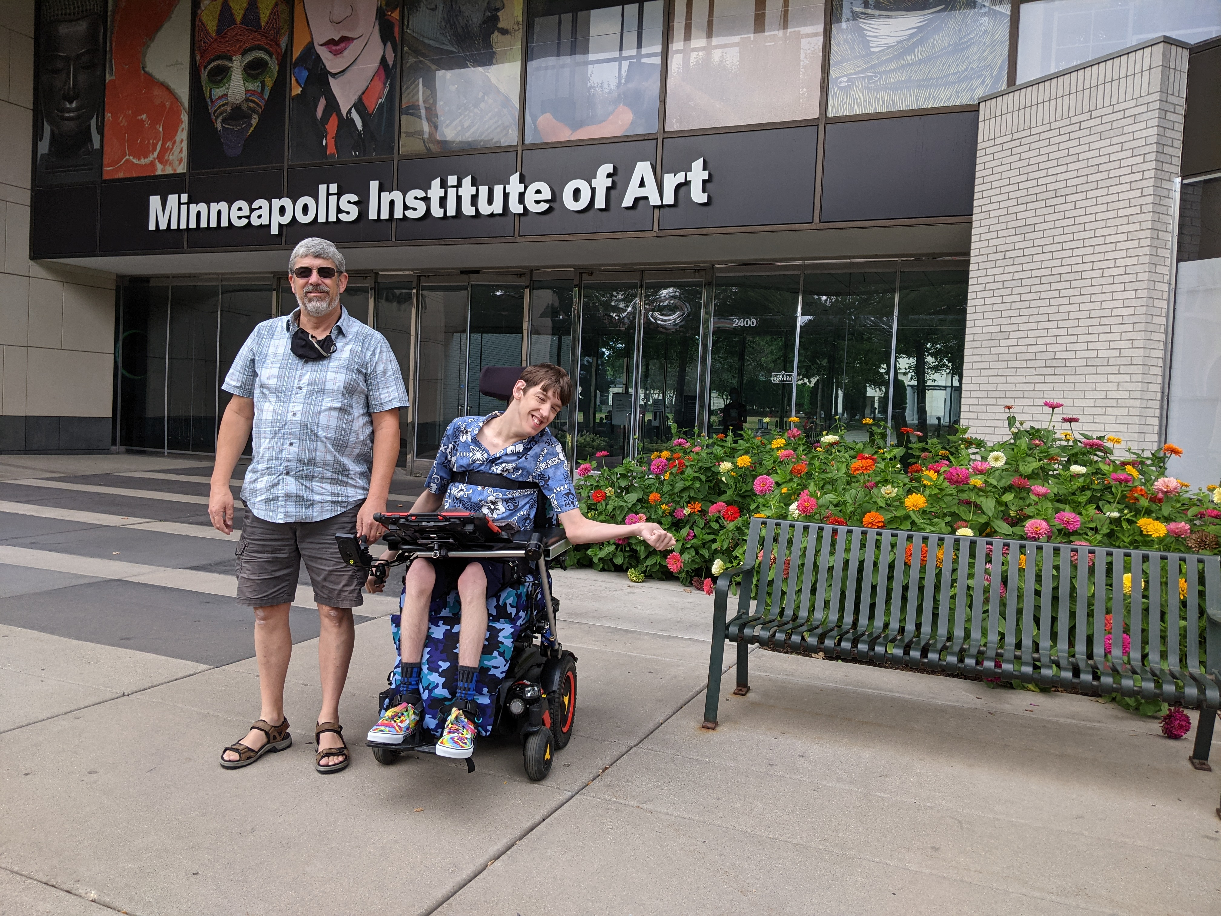 Justin in wheelchair, his dad, in front of Minneapolis Institute of Arts entrance, dahlias blooming