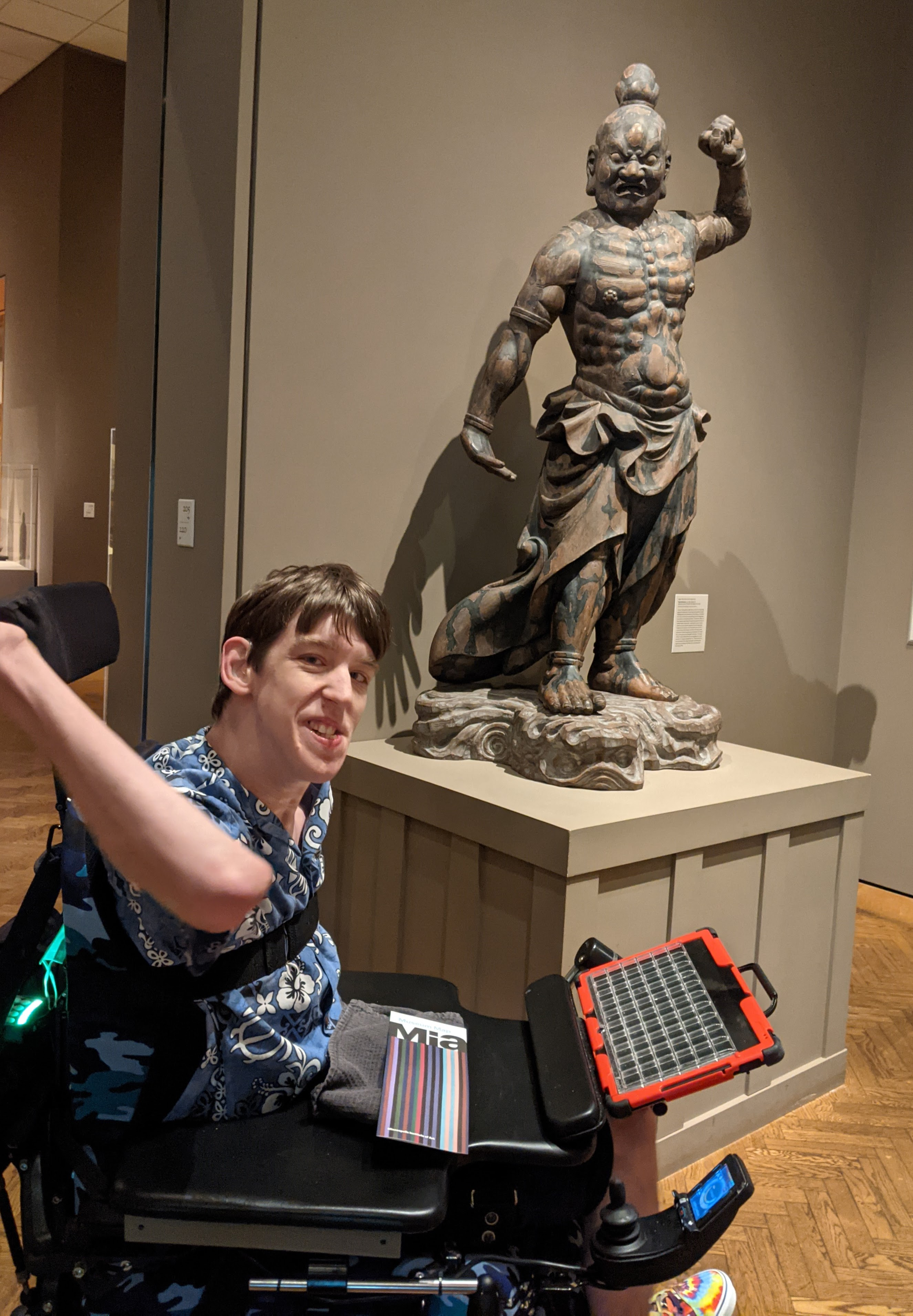 Justin in wheelchair holding up fist and grimacing similar to Japanese Vajra Warrior sculpture
