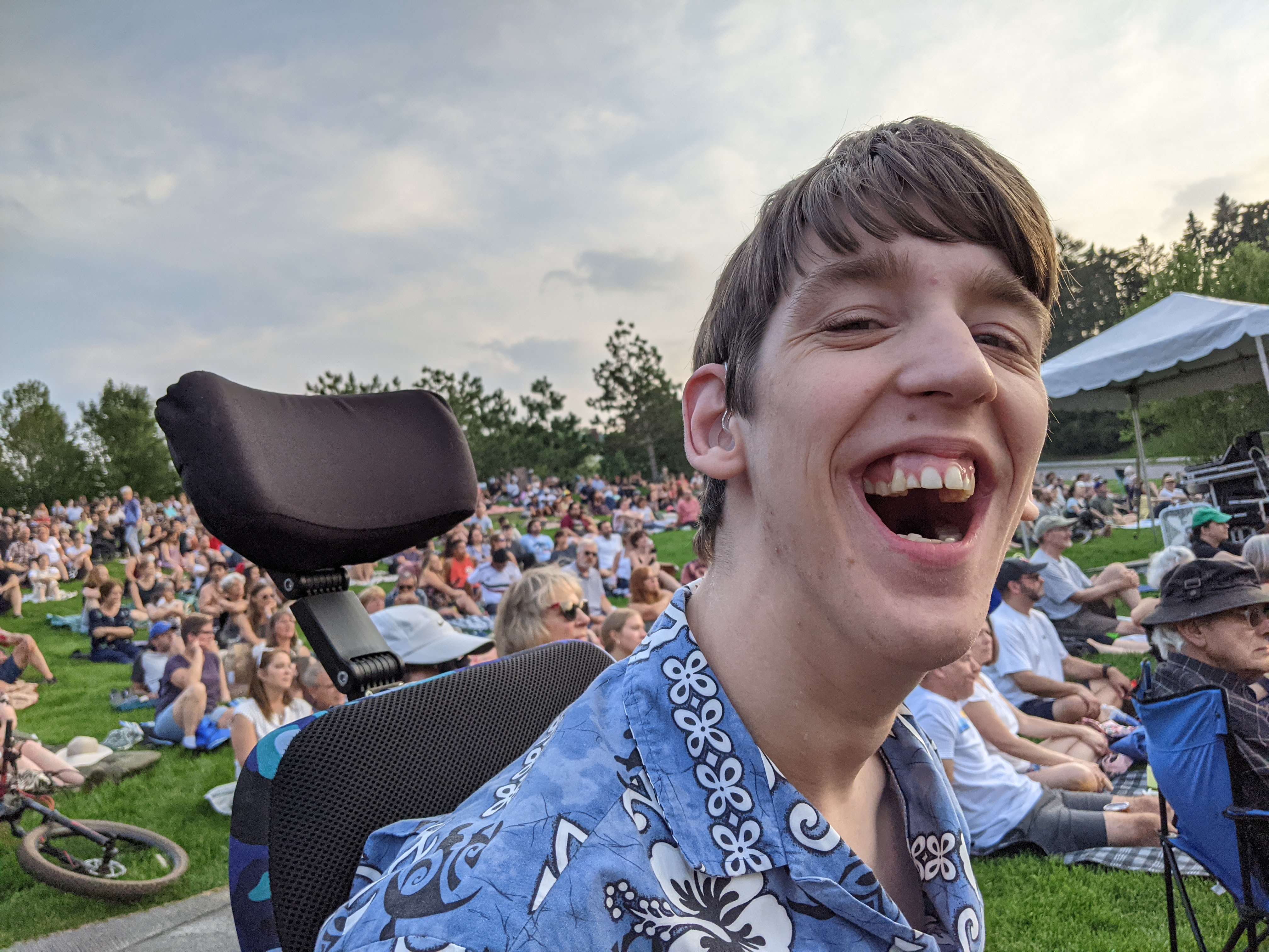 Justin in wheelchair, laughing, hillside behind filled with people watching jazz concert