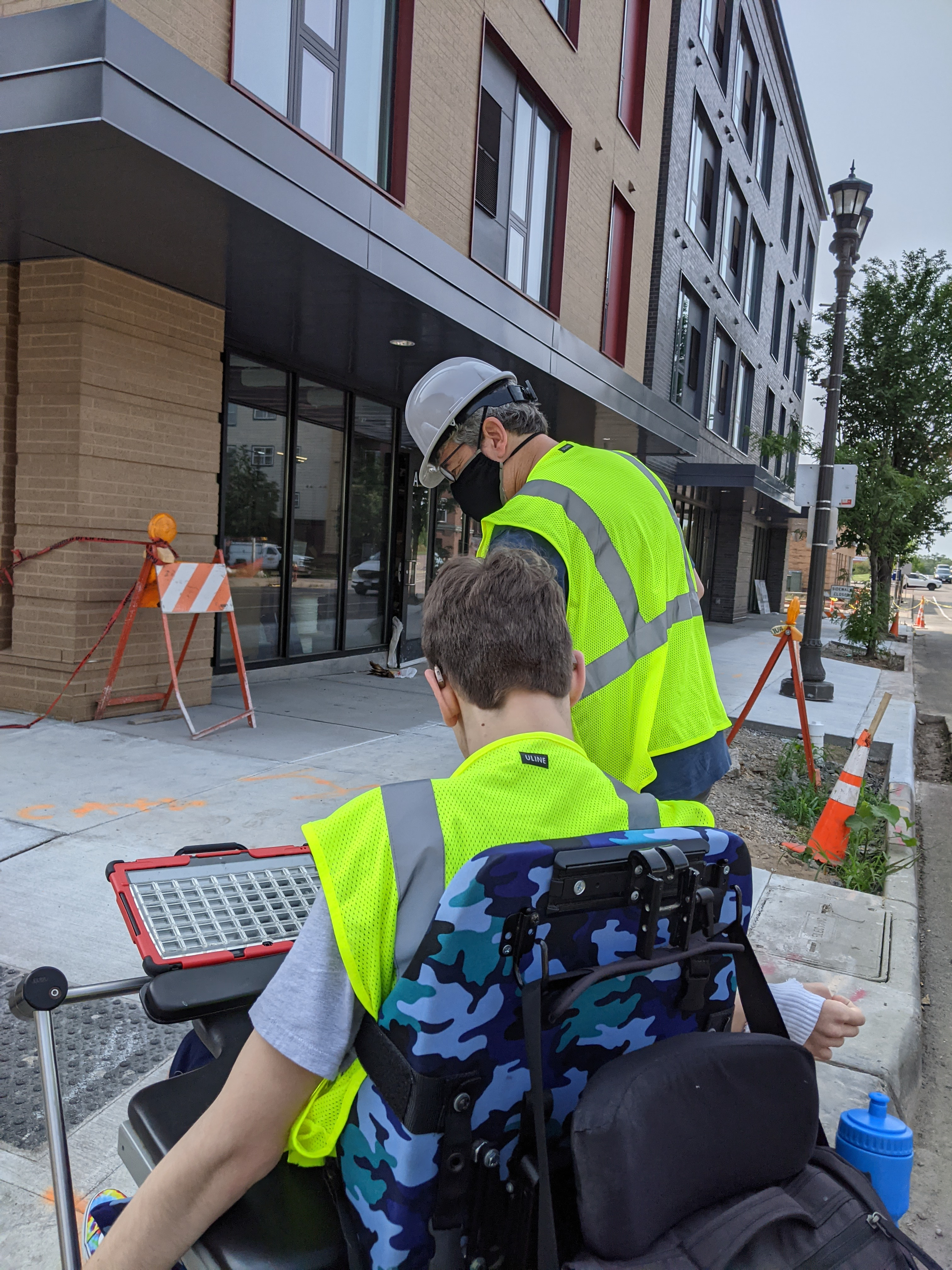 Back of masked man with hard hat and yellow vest, back of young man in wheelchair with yellow vest on, apartment building, construction cones